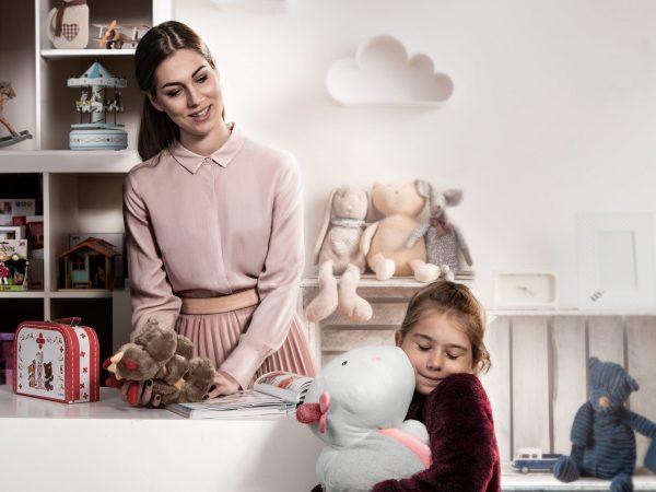 Sieviete bērnistabā vēlīgi skatās kā meitenīte priecīgi apskauj mīksto rotaļlietu