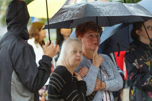 Cilvēki zem lietssargiem