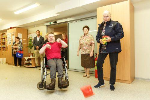 Cilvēks ratiņkrēslā met spilventiņu