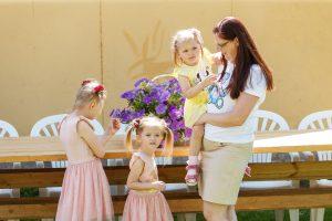 Sieviete stāv pie galda ar trim mazām meitenītēm. Viena no tām viņai ir klēpī