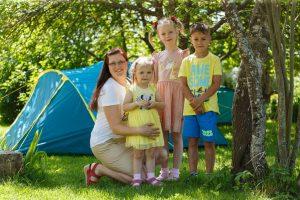 Sieviete dārzā pozē ar trim bērniem. Fonā telts