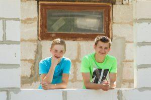 Meitene ar puisi stāv atbalstījušies uz mūra un smaida