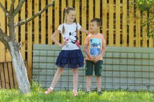 Meitenīte ar puisīti stāv un, smaidot, skatās viens uz otru