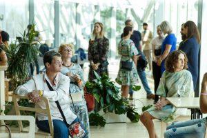 Cilvēki telpā runā un gaida pasākuma atklāšanu