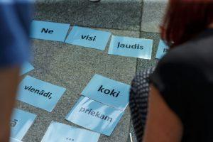 Uz zemes izliktas lapas ar dažādiem vārdiem