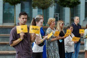 Cilvēki sastājušies rindā, tur sev pirekšā dzeltanas lapiņas ar dažādiem vārdiem
