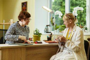 Divas kundzes sēž pie galda un apspriežas