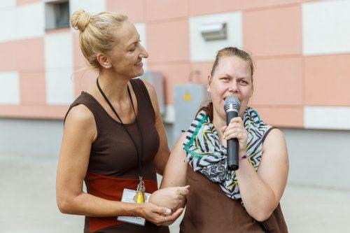 Divas sievietes. Viena no tām, grupu dzīvokļa iemītniece, runā mikrafonā