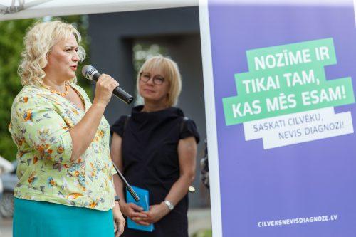 Divas sievietes, viena no tām runā mikrafonā. Fonā kampaņas