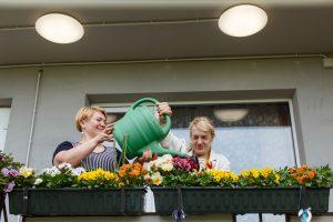 Divas kundzes uz balkona laista ziedus