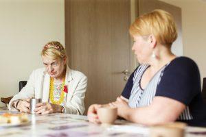 Divas kundzes pie galda runājas