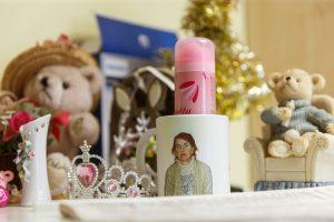 Bižutērija, krūzīte ar Ārijas portretu, dekoratīva svece, viss uz galda virsmas tuvplānā