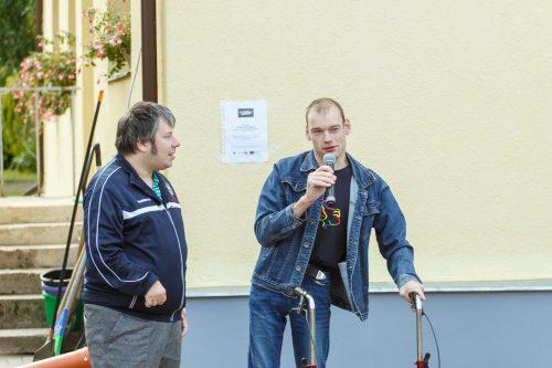 Divi vīrieši. Viens no tiem atbalstās pret ratiņiem un runā runu