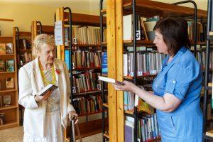 Ārija biliotēkā stāv un sarunājas ar bibliotekāri