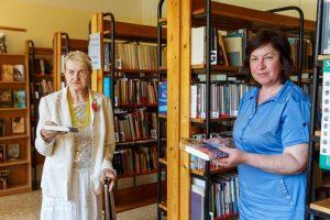Ārija ar bibliotekāri bibliotēkā pozē kamerai