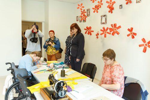 apmeklētāji apskata rosību dienas aprūpes centra darbnīcā