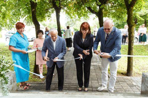 Sarkanā krusta prezidents, labklājības ministra padomniece un Valkas mērs svinīgi girež lentīti, lai atklātu gurpu dzīvokļu māju