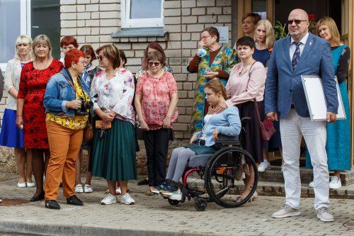 Viesi un grupu dzīvokļu iemītnieki sapulcējušies mājas pagalmā