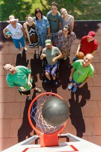 Cilvēki sporta laukumā skatās augšup. Skats no augšas, no basketbola groza