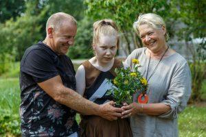 Alise ar ziediem rokā un vecākiem pie abiem sāniem