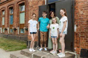 Ģimene, mamma trīs meitas un dēls pie mājas durvīm stāv un pozē fotogrāfam