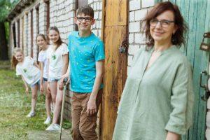 Trīs pusaudži, Renārs ar māsām, un mamma pozē pie šķūnīšiem