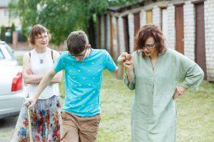 Pusaudzis, Renārs, pieturoties pie mātes rokas iet bez spieķīša. Aiz viņiem iet sieviete