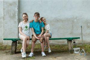 Pusaudži, renārs ar divām māsām sēž uz soliņa