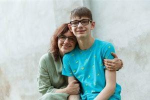 Sieviete ar dēlu sēdus smaidot pozē kamerai