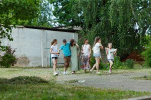 Pusaudži, Renārs ar māsām, mamma un vēl viena sieviete smaidīgi pastaigājas pa ceļu