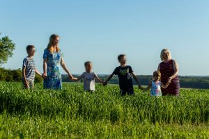 Divas sievietes ar četriem bērniem sadevušies rokās stāv pļavā