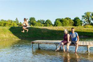 Dīķis vasarā. Vecāki sēž uz laipas, puika lec no laipas ūdenī