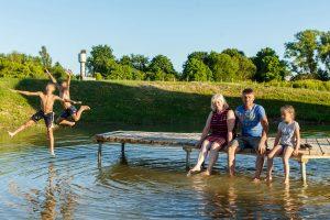 Vasara. Dīķis. Vecāki ar vienu bērnu sēž uz laipas. Divi bērni lec no laipas ūdenī.