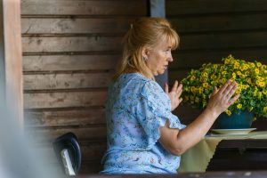 Sociālā centra vadītāja sēž lapenē un aprūpē puķes podiņā
