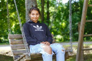 Meitene sēž šūpolēs
