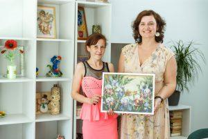 Nataša ar sociālo darbinieci stāus pozē turot Natašas gleznu rokās