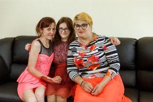 Trīs sievietes, sēžot dīvānā, pozē