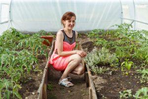 Nataša siltumnīcā pietupusies pie augiem