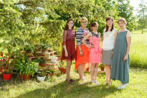 Piecas sievietes, stāvot pļavā, pozē pie kokiem