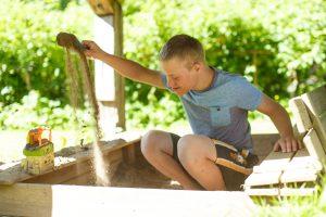 Ginters spēlējas ar smiltīm smilškastē