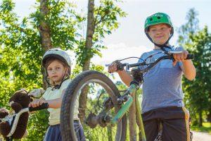 Ginters ar māsu uz velosipēdiem. Ginters pacēlis priekšējo ratu gaisā