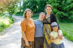 Ginters ar mammu, vecmāmiņu un māsu apskāvušies stāv uz lauku ceļa
