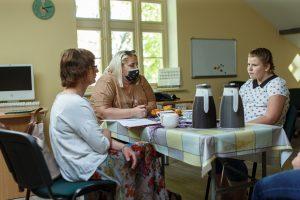 Divas sievietes un Katelīna sēž istabā pie klāta galda