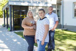 Ketlīna  ar vecākiem stāv uz troturāra