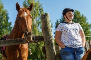 Ketlīna ar zirgu stāv pie zigru aploka žoga