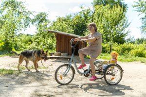 Lelde uz velosipēda pie suņa un suņabūda