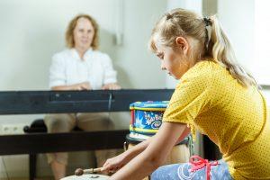 Keita spēlē bungas. Fonā skolotāja spēlē uz sintezatora.