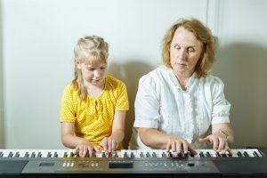 Keita ar skolotāju spēlē uz sintezatora