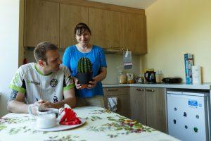 Ingus sēž virtuvē pie galda. Aiz viņa Inga stāv ar lielu kaktusu podiņā rokās