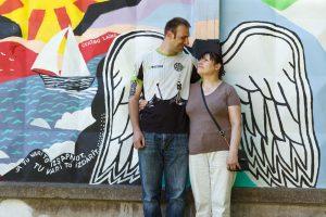 Inga un Ingus stāv pie grafiti sienas